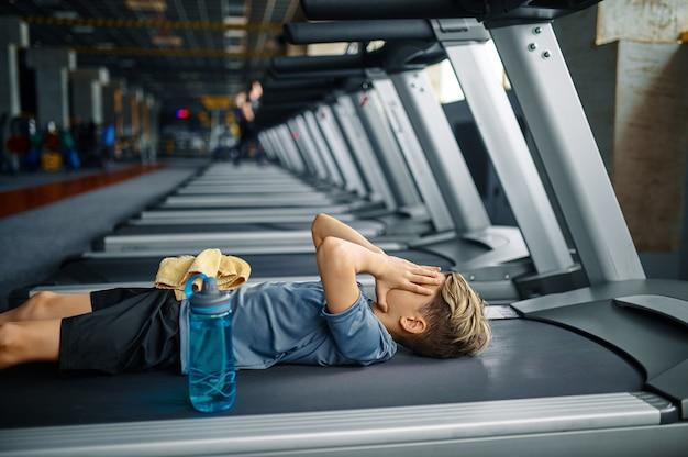 Zmęczony młodzieniec leżący na bieżni w siłowni, uruchomiona maszyna. chłopiec na treningu w klubie sportowym, ochronie zdrowia i zdrowym stylu życia, uczeń na treningu