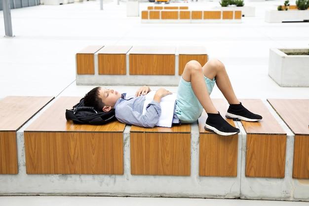 Zmęczony nastolatek uczeń śpi po zajęciach na boisku szkolnym kampusu na drewnianej ławce z tornisterem pod głową.