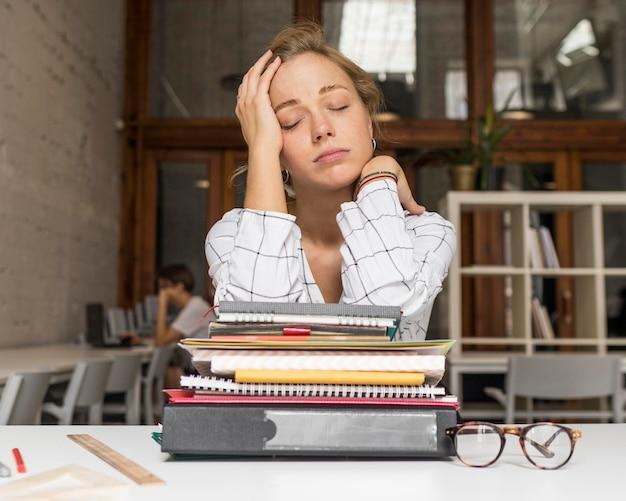 Zmęczony nauczyciel ze stosem książek na biurku