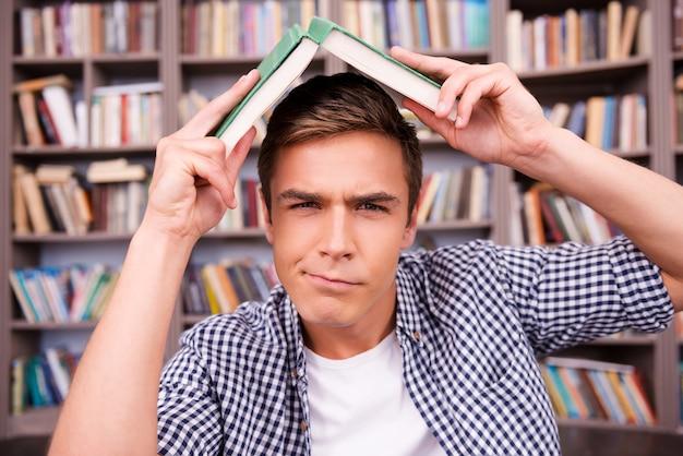 Zmęczony nauką. sfrustrowany młody mężczyzna niosący książkę na głowie i wyrażający negatywne nastawienie, siedząc przy półce z książkami
