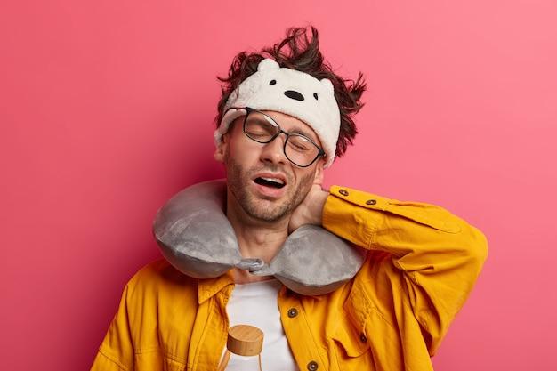 Zmęczony nieogolony mężczyzna cierpi na sztywność karku, przechyla głowę, nosi poduszkę podróżną