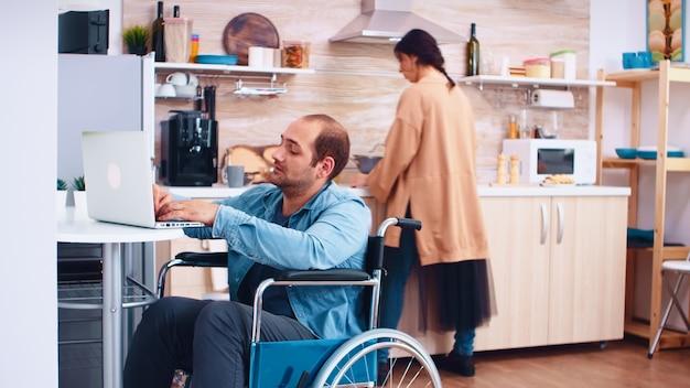 Zmęczony niepełnosprawny mężczyzna na wózku inwalidzkim, pracujący na laptopie w kuchni i żona gotuje posiłek. biznesmen z paraliżem, niepełnosprawnością, niepełnosprawnością, niepełnosprawnością, trudnościami w pracy po wypadku, z dostępem do internetu