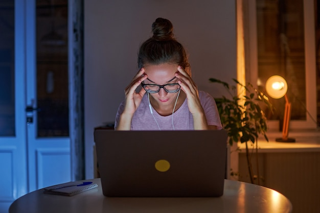 Zmęczony niepokój podkreślił pracoholiczkę cierpiącą na bóle głowy podczas siedzącej późnej pracy przy komputerze