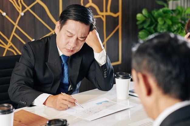 Zmęczony niezadowolony biznesmen badanie sprawozdania finansowego po kryzysie finansowym