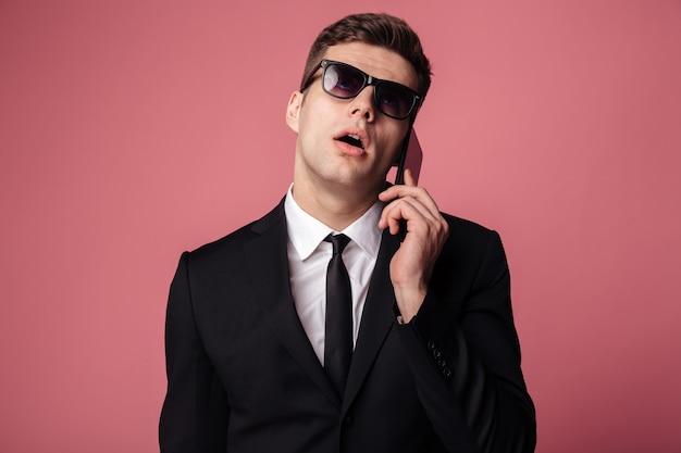 Zmęczony niezadowolony młody biznesmen rozmawia przez telefon komórkowy.