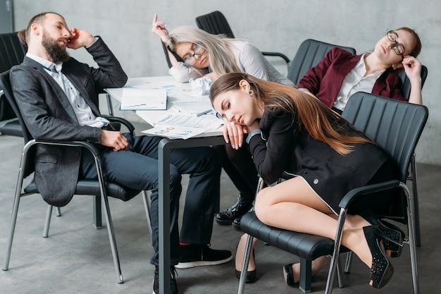 Zmęczony personel korporacyjny. koncepcja przepracowania. członkowie zespołu firmy spanie na biurku i krzesłach.