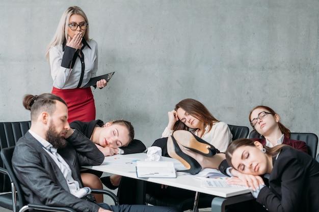 Zmęczony personel korporacyjny. koncepcja przepracowania. kolega przygląda się członkom zespołu śpiącym na biurku i krzesłach.