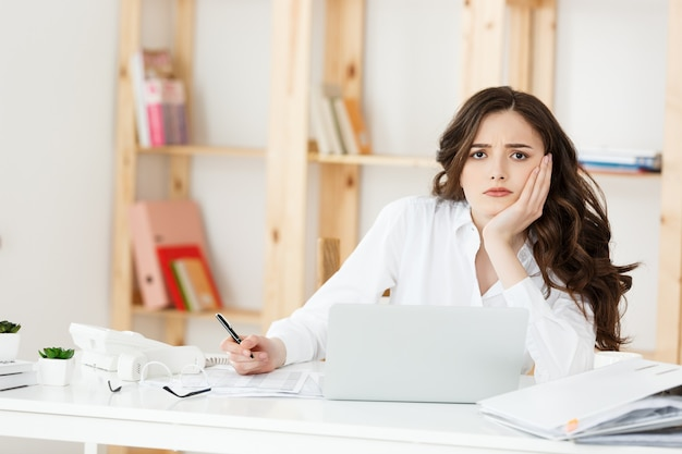 Zmęczony piękna kobieta trzymając rękę na głowie podczas pracy na komputerze i niektóre dokumenty biznesowe w jasnym biurze