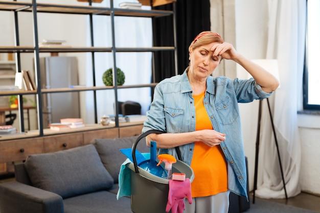 Zmęczony podczas sprzątania. dopasuj jasnowłosą kobietę zaniepokojoną ilością pracy jaką wykonuje podczas sprzątania