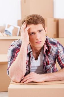 Zmęczony poruszaniem się. przygnębiony młody mężczyzna siedzi na podłodze i trzyma rękę we włosach, podczas gdy kartony leżą w tle