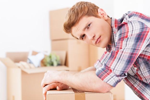 Zmęczony poruszaniem się. widok z boku przygnębionego młodego mężczyzny pochylającego się nad kartonowym pudełkiem i wyrażającego negatywność, podczas gdy w tle leży więcej pudeł