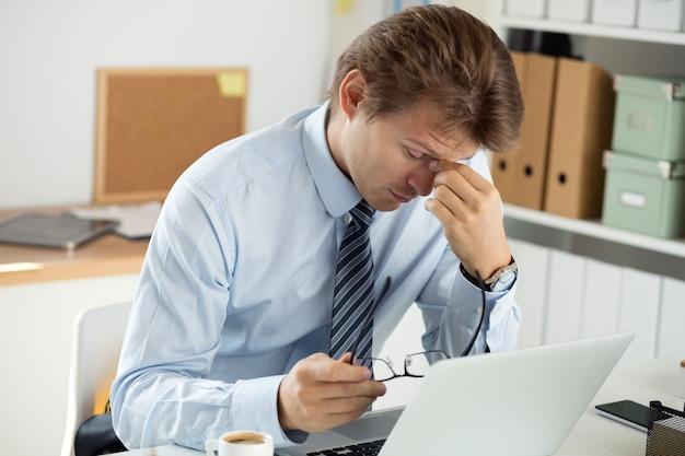Zmęczony pracownik biurowy dotykający grzbietu nosa, aby dać odpocząć oczom i skoncentrować się. księgowy sporządzający sprawozdanie finansowe. termin i koncepcja przepracowania.