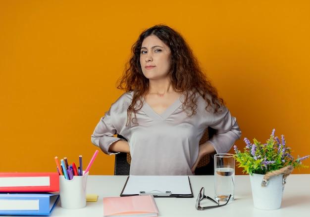 Zmęczony pracownik biurowy młodych całkiem żeński siedzi przy biurku z narzędzi biurowych, kładąc ręce na plecach na białym tle na pomarańczowy