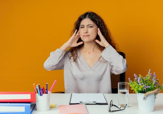 Zmęczony pracownik biurowy młodych całkiem żeński siedzi przy biurku z narzędzi biurowych, kładąc ręce na szyi na białym tle na pomarańczowy