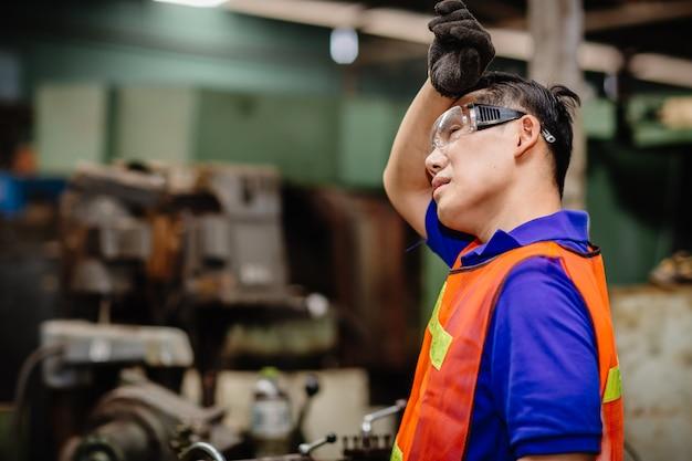 Zmęczony pracownik, ból głowy gorąca pogoda nad upałem niezdrowego inżyniera pracującego w fabryce przemysłu ciężkiego.
