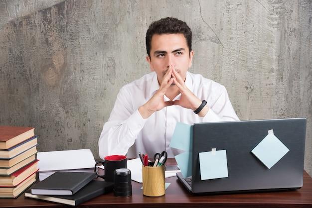 Zmęczony pracownik myśli o pracy przy biurku.