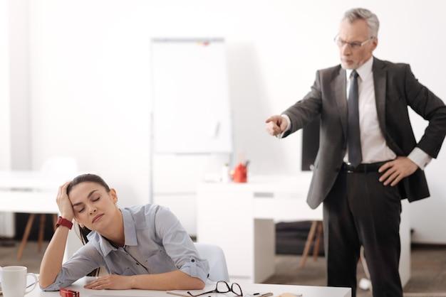 Zmęczony pracownik ślizgający się w miejscu pracy, marząc o wakacjach, trzymając ręce na stole