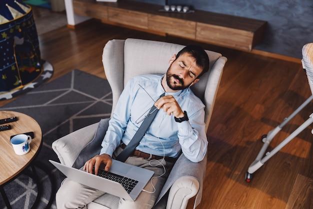 Zmęczony pracujący ojciec siedzi w salonie i trzymając laptopa na kolanach