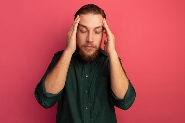 Zmęczony przystojny blondyn stoi z zamkniętymi oczami kładąc ręce na skroniach na białym tle na różowej ścianie