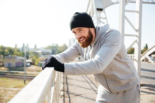 Zmęczony przystojny młody sportowiec stojący i odpoczywający na miejskim moście