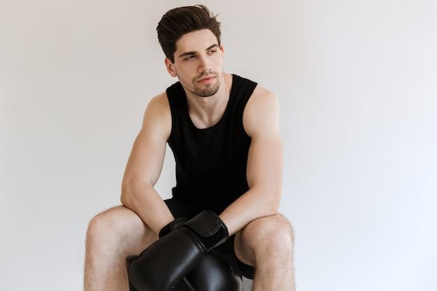 Zmęczony przystojny silny młody sportowiec bokser w rękawiczkach siedzi i odpocząć na białym tle.