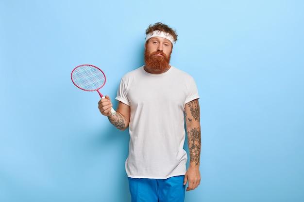 Zmęczony rudowłosy tenisista trzyma rakietę, pozując przy niebieskiej ścianie