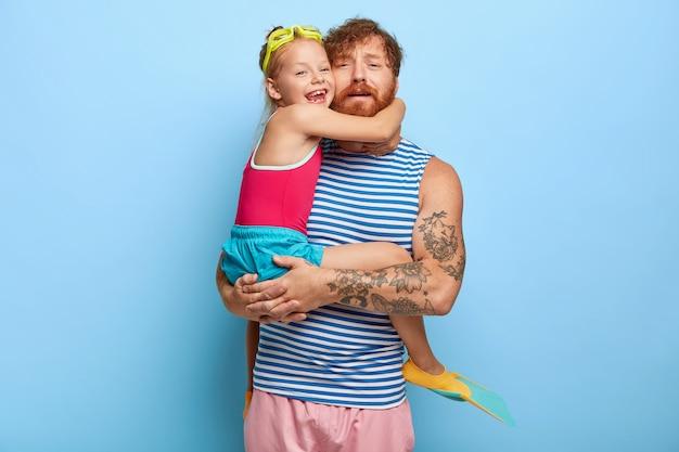 Zmęczony rudy ojciec i córka pozują w strojach basenowych