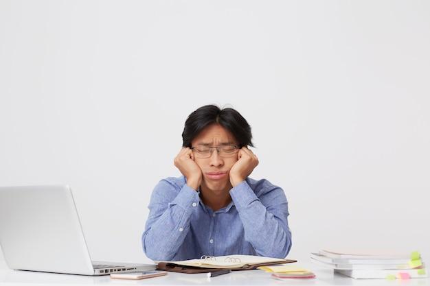 Zmęczony senny azjatycki młody biznesmen w okularach z głową na rękach siedzi i spanie w miejscu pracy przy stole nad białą ścianą