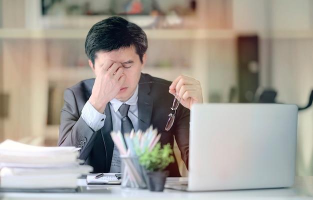 Zmęczony sfrustrowany biznesmen czuje się zestresowany, trzymając głowę i martwiąc się o niepowodzenie problemów biznesowych.