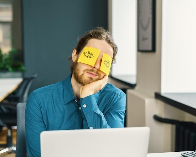 Zmęczony śpiący młody męski pracownik biurowy ukrywający oczy z zabawnymi karteczkami samoprzylepnymi