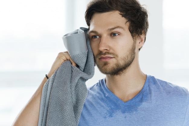 Zmęczony spocony mężczyzna z ręcznikiem po treningu fitness na siłowni