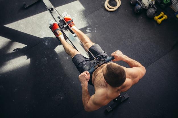 Zmęczony sportowy trening męski na maszynie do ćwiczeń siłowych w klubie siłowni