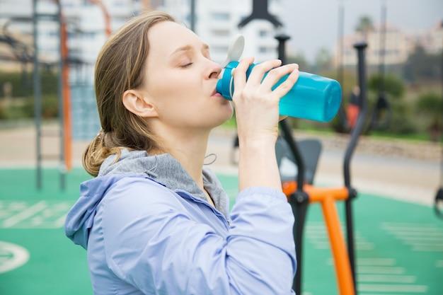Zmęczony sprawny dziewczyna czuje się spragniony podczas ćwiczeń fizycznych