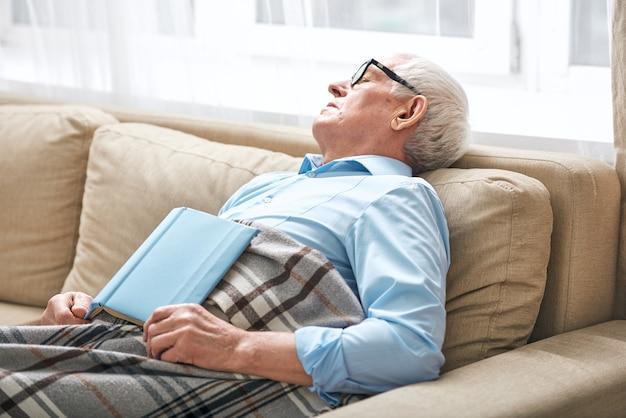 Zmęczony starszy mężczyzna przykryty kratą drzemiący na kanapie z otwartą książką, której nie skończył i zasnął podczas pobytu w domu