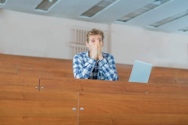Zmęczony student śpi w sali wykładowej b