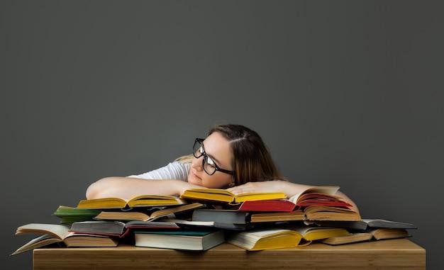 Zmęczony student w okularach śpi na książkach w bibliotece