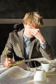 Zmęczony student zdejmuje okulary i pociera oczy podczas przerwy kawowej w restauracji