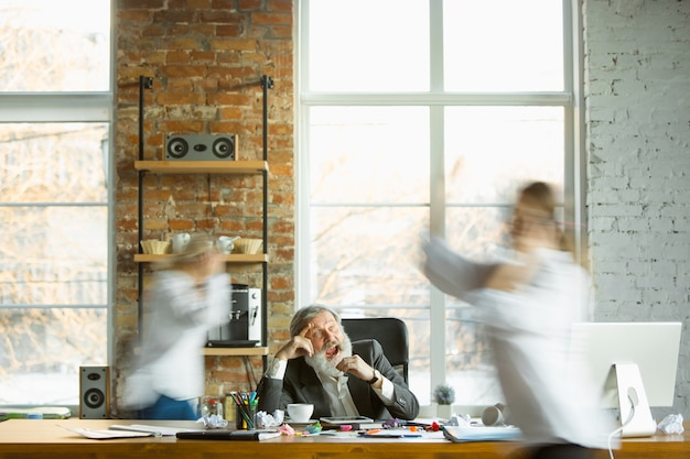 Zmęczony szef odpoczywa w swoim miejscu pracy, podczas gdy zajęci ludzie poruszają się w pobliżu niewyraźne. pracownik biurowy, kierownik pracujący, pijący kawę i udzielający wskazówek kolegom. biznes, praca, koncepcja obciążenia pracą.