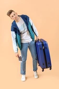 Zmęczony turysta mężczyzna z bagażem w kolorze beżowym