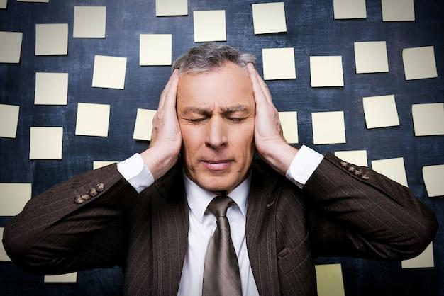 Zmęczony tym wszystkim. sfrustrowany starszy mężczyzna w formalnym stroju trzymający głowę w dłoniach i trzymający zamknięte oczy, stojąc przed tablicą z samoprzylepnymi notatkami