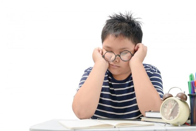 Zmęczony uczeń chłopiec z okularami śpi na książkach