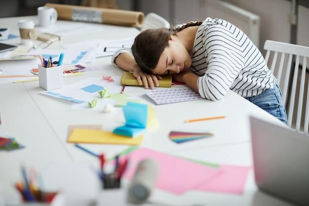 Zmęczony uczeń śpi na biurku