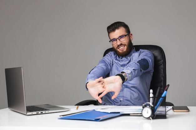 Zmęczony uśmiechnięty brodaty elegancki mężczyzna w okularach rozgrzewa się siedząc przy stole w biurze