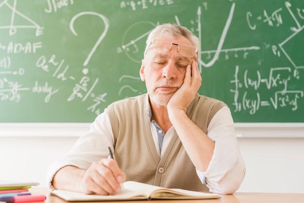 Zmęczony wieku nauczyciel matematyki śpi przy biurku