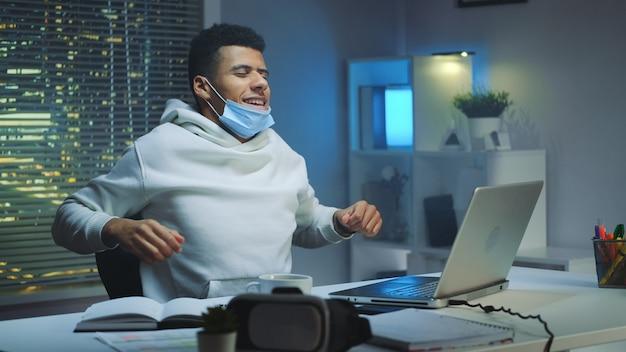 Zmęczony wieloetniczny mężczyzna z maską ochronną pracuje w domu późno w nocy i rozgrzewa
