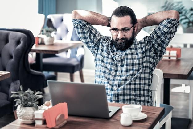 Zmęczony wolny strzelec. brodaty ciemnowłosy freelancer w okularach czuje się zmęczony po długiej pracy