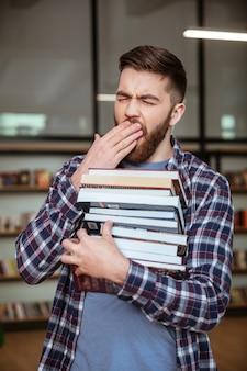 Zmęczony wyczerpany mężczyzna trzyma stos książek i ziewanie