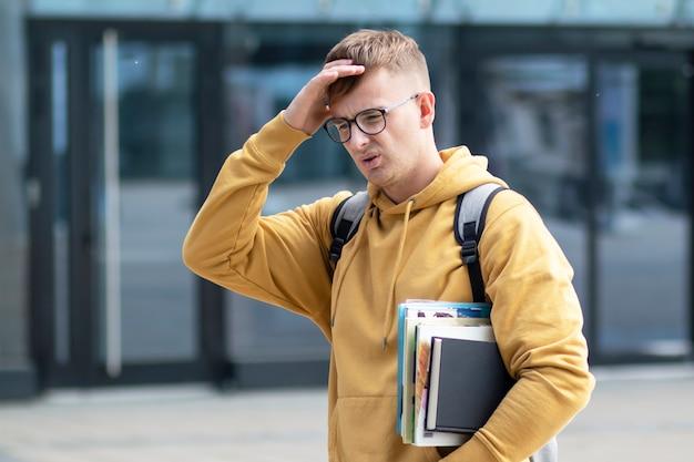 Zmęczony wyczerpany student uniwersytetu, młody chłopak, mężczyzna z książkami, podręczniki cierpiące z powodu ciężkiej pracy lub bólu głowy, migrena, trzymająca głowę ręką. przepracowany uczeń, problemy z nauką, porażka
