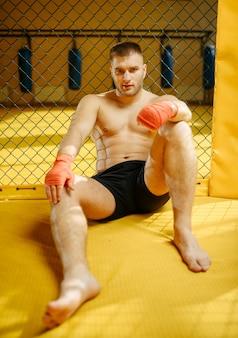 Zmęczony zawodnik mma siedzi na podłodze w klatce na siłowni.