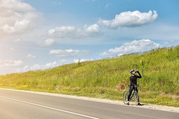 Zmęczony zawodowy sportowiec pije wodę odpoczywając na wyścigu rowerowym na torze